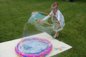 Summer Fun - child making bubbles with a hula hoop