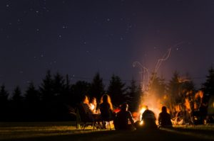 People sitting around a campfire at night.