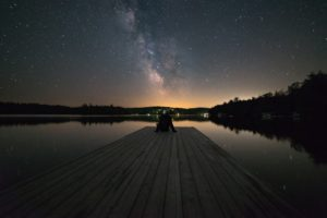 Man sitting on a dock under a night sky.