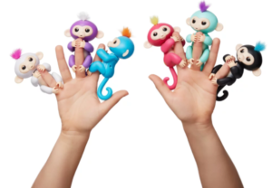 Two hands holding Fingerlings baby monkey toys